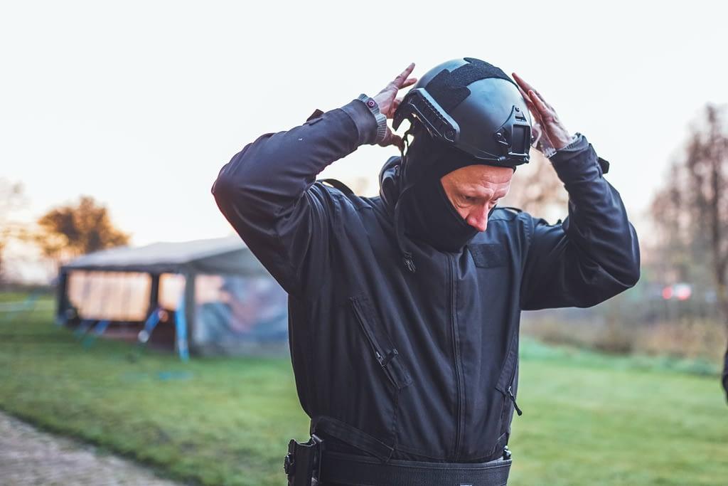 Een deelnemer van de Special Forces Experience doet zijn helm en bivakmuts af na de persoonlijk ontwikkeling training